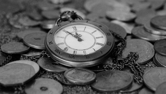 Relógio antigo em cima de moedas representa como otimizar a gestão de negócio