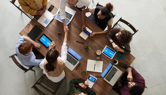 Mesa com pessoas fazendo reunião vista de cima representa a pesquisa de satisfação do cliente