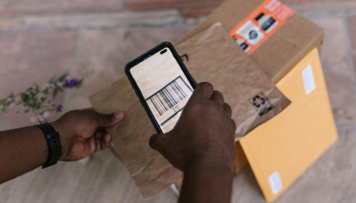 Manos de una persona escaneando el código de barras de un paquete
