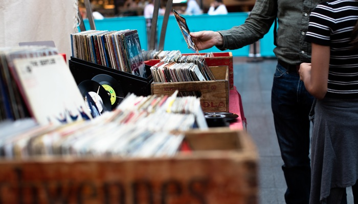 Pessoas escolhem CDs em caixas, representando os primeiros passos de vender online