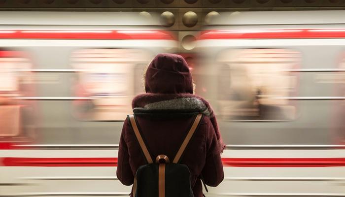 Mulher de costas para câmera em frente a metrô representa as profissões digitais