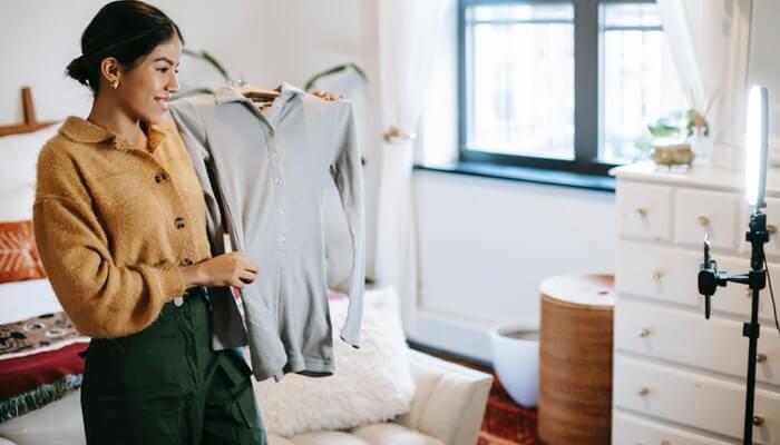 Mulher segurando blusa em cabide em frente a ring light representa a oferta de produtos