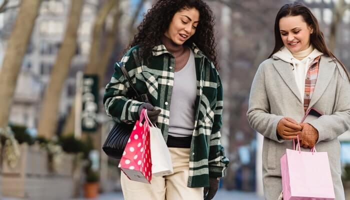 Duas mulheres seguram sacolas e sorriem, representando a prova social