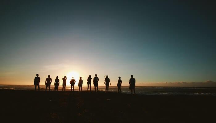 Pessoas em praia contra o sol representando público-alvo