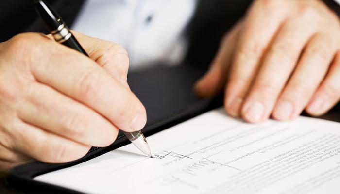Mãos assinando contrato de serviços digitais