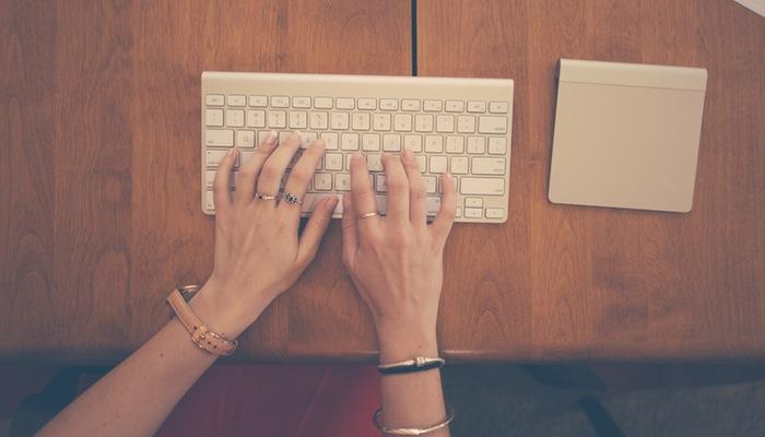 Mulher digita em teclado de computador, representando o Speaklyn