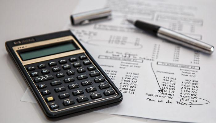 Una calculadora, una hoja de papel con cifras y un bolígrafo