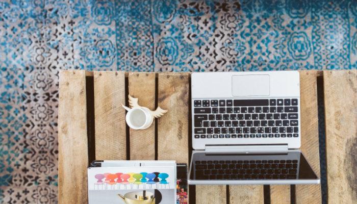 Notebook sobre mesa de madeira com chão de ladrilhos coloridos ao fundo representa o trabalho remoto