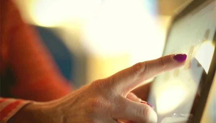 Mulher clicando em tela touch representa a usabilidade