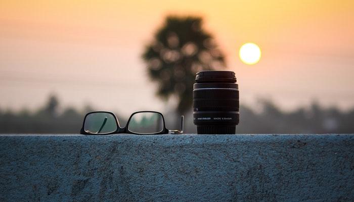 Óculos e lente sobre mureta ao pôr do sol representam vender no Instagram