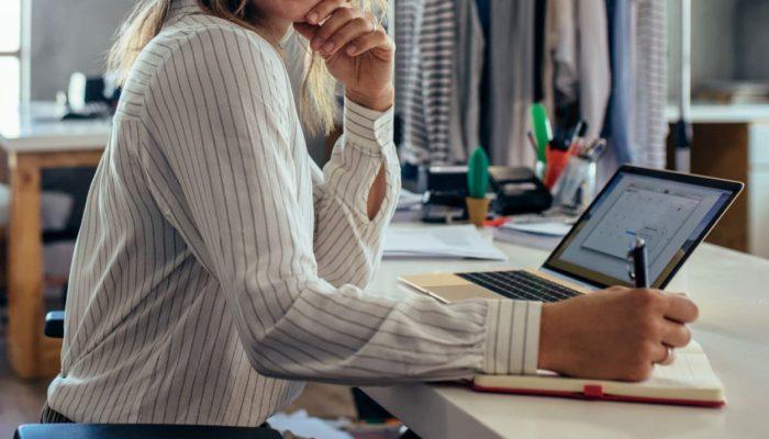 Mujer tomando nota en un cuaderno frente a una laptop
