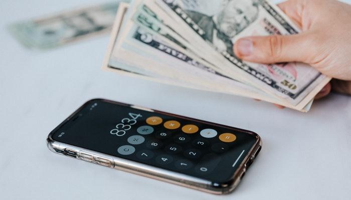 Imagem mostrando uma pessoa contando notas de dinheiro com uma calculadora, simbolizando como aumentar as vendas no Mercado Livre.