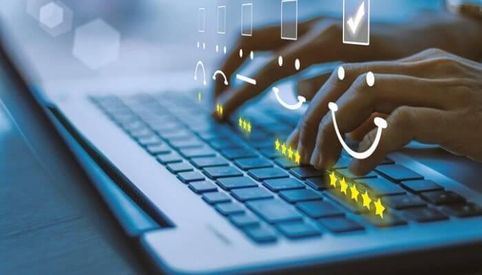 imagem mostra mãos digitando em um computador. Na imagem aparece, também, ilustrações de clientes satisfeitos, resultado de um trabalho de captação de clientes