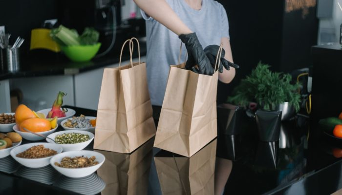 Persona con guates guardando comida para llevar en bolsa de cartón