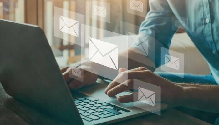 imagem mostra mãos digitando em um computador, criando uma campanha de e-mail em uma ferramenta grátis de e-mail marketing