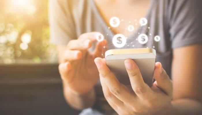 Imagem mostra mãos segurando um smartphone, simulando uma transação, por um meio pagamento online