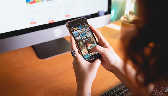 Imagem mostrando uma pessoa acessando um site através do celular, representando a importância do mobile first.