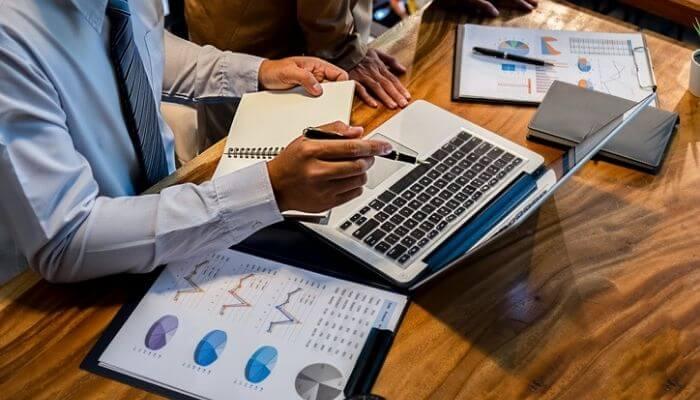 imagem mostra uma mão segurando uma caneta apontada para a tela do PC, com relatórios espalhados pela mesa, simulando o teste de uma nfe em um ambiente de homologação