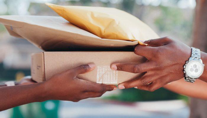 Persona entregando un paquete a otra persona en logística de última milla