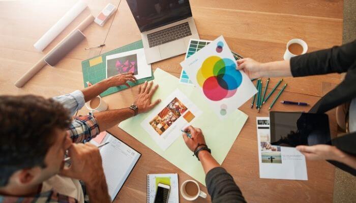 TTime definindo cores, imagens e estratégias em uma mesa, representando o branding