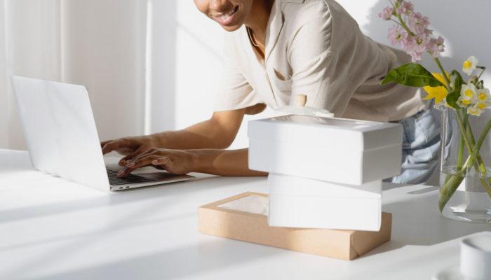 Mujer escribiendo en laptop con productos empacados a un lado