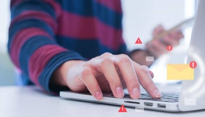 imagem mostra um computador com ilustrações de e-mail marketing considerados SPAM
