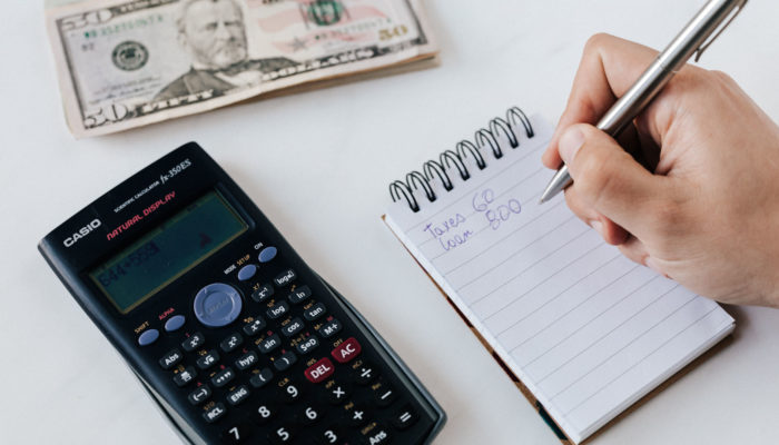 Persona haciendo fijación d eprecios con una calculadora y una libreta