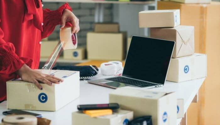 imagem mostra um fornecedor de produtos para revenda embalando uma caixa, ao lado de um computador
