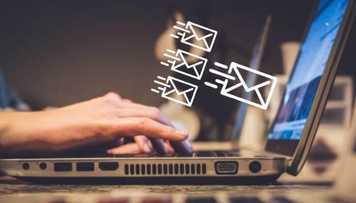 Mãos em um computador simulando a criação de uma campanha de e-mail marketing no MailChimp