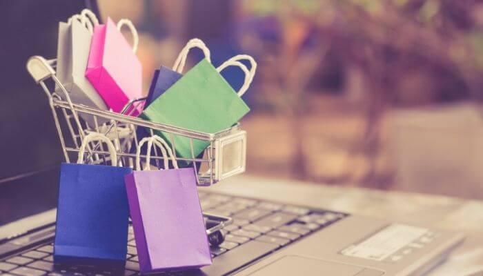 imagem representa figuradamente como montar uma loja virtual: computador aberto com um carrinho de compras em cima