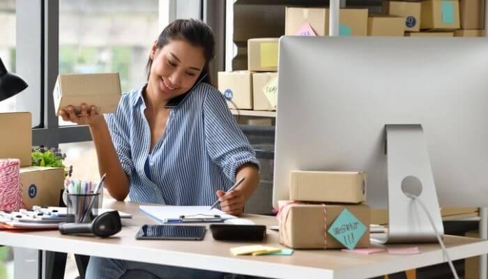 mulher em uma ligação telefônica, sentada em frente a um computador, representando como administrar uma loja virtual