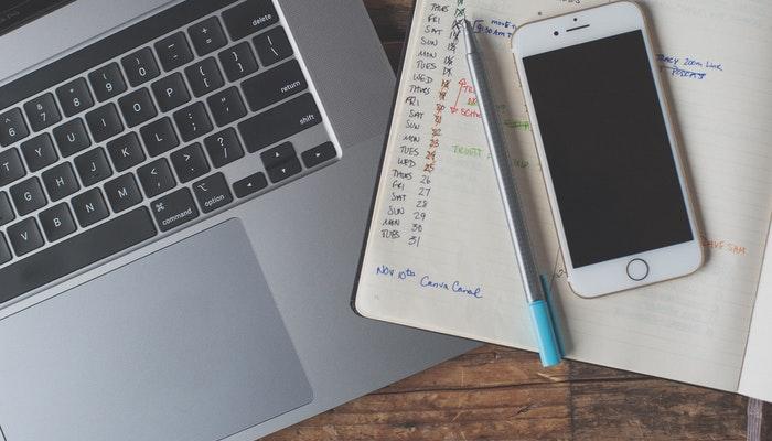 Imagem mostrando um celular sobre um bloco de notas e um laptop, representando a elaboração de um calendário editorial.
