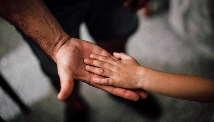 Imagem mostrando as mãos de uma criança sobre as mãos de um homem, representando uma campanha de dia dos pais.