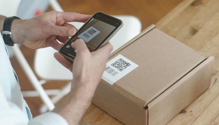 persona escaneando una etiqueta con código de barras y código QR con un smartphone