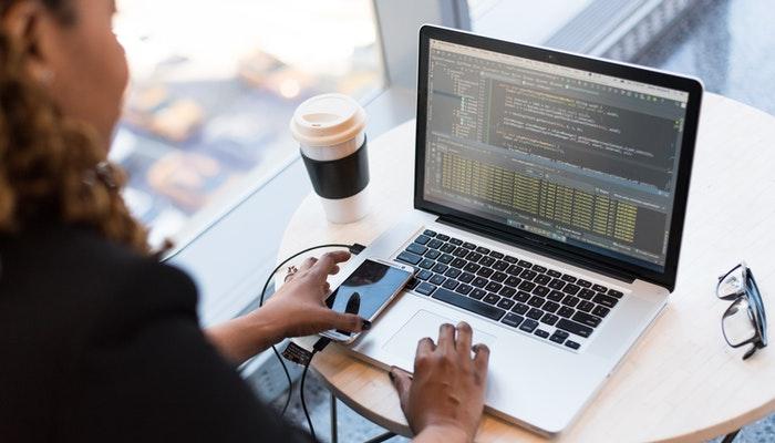 Imagem mostrando uma mulher usando um notebook para criar um site.