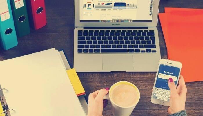 uma mão segura um celular com o aplicativo do facebook aberto, a outra segura um café. A imagem representa o processo criativo para fazer marketing no facebook