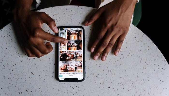 Imagem mostrando um usuário olhando um catálogo por meio de um smartphone, representando como vender pelas redes sociais.