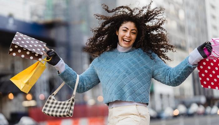 Imagem mostrando uma mulher carregando sacolas de compra, representando as etapas da jornada do cliente.