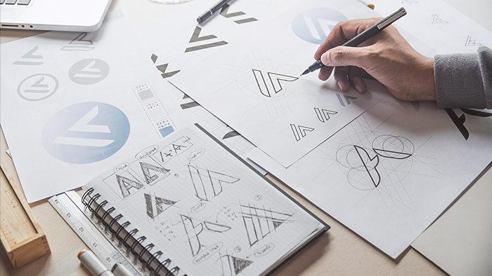 Pessoa desenhando o logotipo de uma empresa para representar marca registrada.