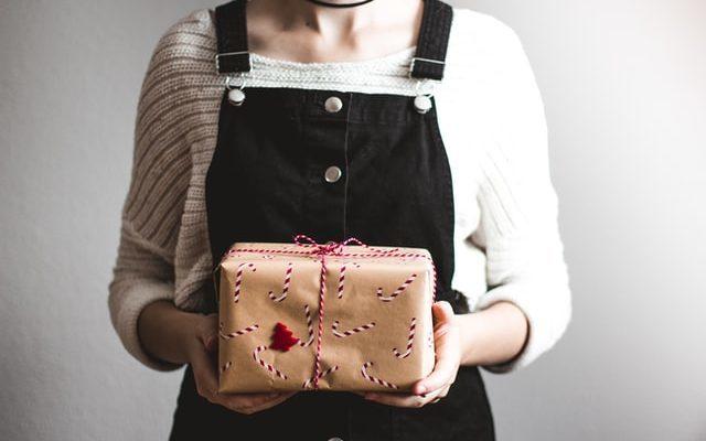 Imagem mostrando uma mulher segurando um pequeno pacote, simbolizando o envio via PAC Mini.