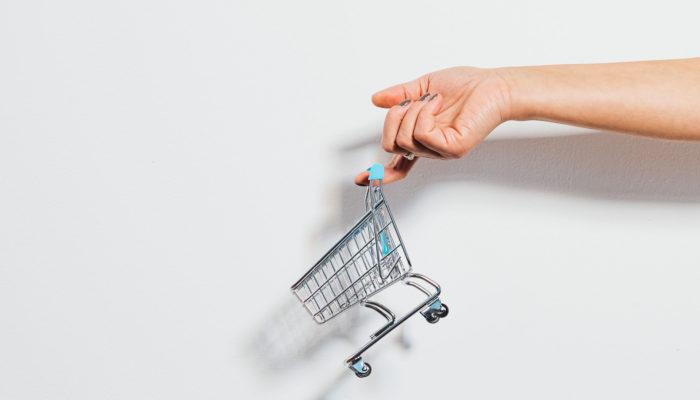 Mano sosteniendo un carrito de supermercado