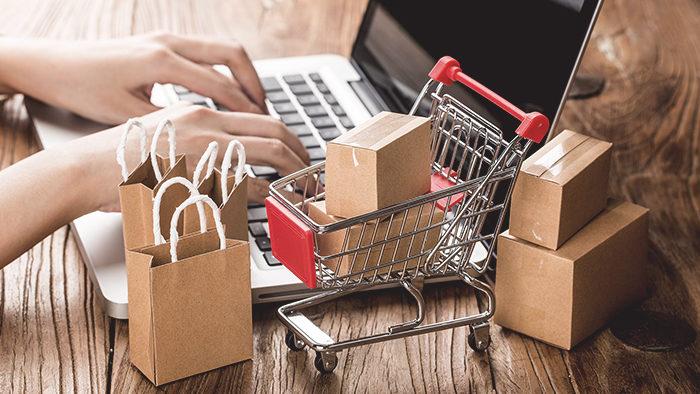 Imagem com pessoa fazendo compras online e notebook com miniatura de carrinho de compras para representar produtos mais vendidos no Mercado Livre.