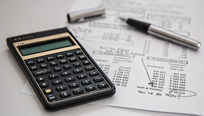 Imagem mostrando uma calculadora sobre papéis com diversos cálculos, simbolizando um plano de redução de custos.