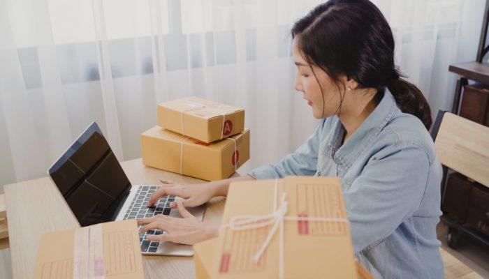 El control de inventarios de una emprendedora frente a la computadora con paquetería y cajas al lado