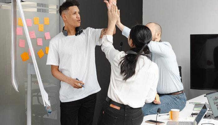 Imagem mostrando pessoas comemorando em uma sala de reunião representando como atrair clientes.