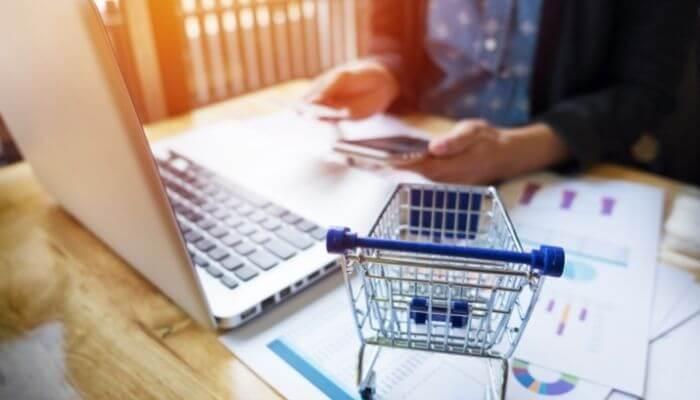 imagem de uma pessoa sentada em frente ao computador, conferindo o passo a passo de como criar uma loja virtual na nuvemshop
