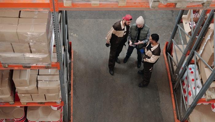 Imagem mostrando homens em um armazém representando o cross docking e dropshipping.