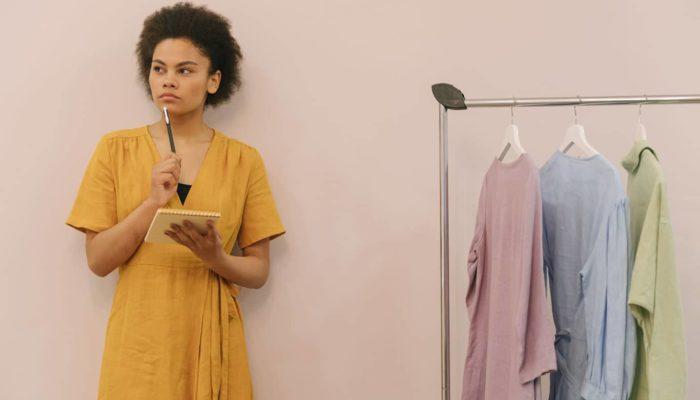 Mujer emprendedora pensando cuál es la diferencia entre persona física y moral junto a un rack de ropa