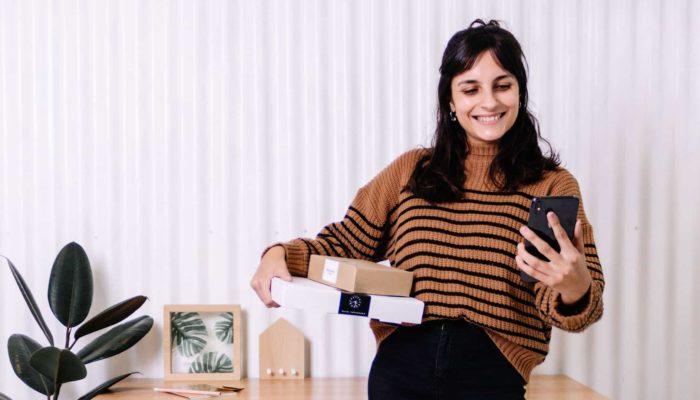 Mujer sosteniendo celular y cajas para emprender en México