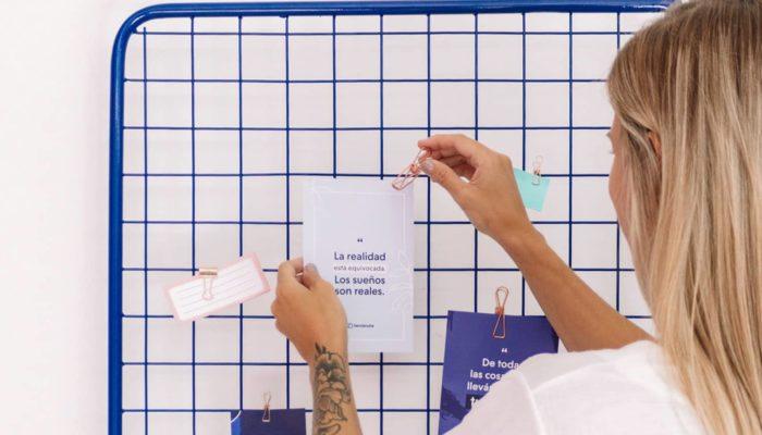 mujer adornando una rejilla con frases de emprendedores